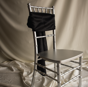 Front of a black chair sash tied into a bow on a silver chair.
