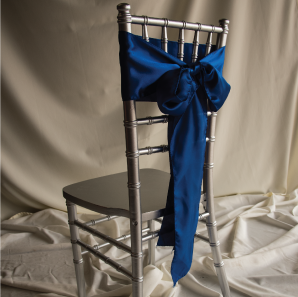Back of a blue chair sash tied into a bow on a silver chair.