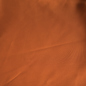 Close up of a burnt orange colored polyester tablecloth.