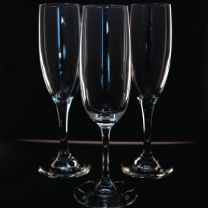 Close up of three champagne glasses in front of a black backdrop.