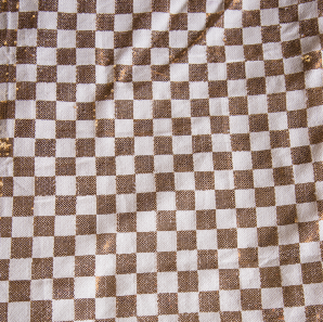 Close up of a champagne and gold checkered sequin tablecloth.