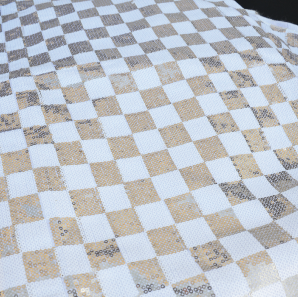 Close up of a champagne and gold checked table runner.