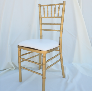 Gold colored Chiavari chair in front of  a white backdrop.