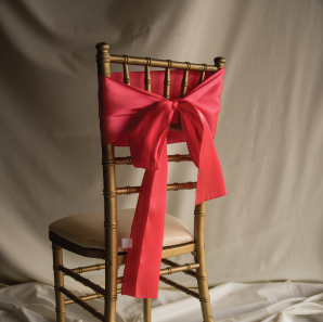 Back of a coral colored chair sash tied into a bow on a silver chair.