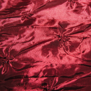 Close up of a pinched crimson red tablecloth.