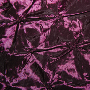 Close up of an eggplant colored pinched tablecloth.