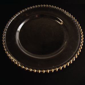Close up of a beaded glass charger on a black tablecloth.