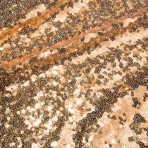 Close up of a gold colored sequined tablecloth.