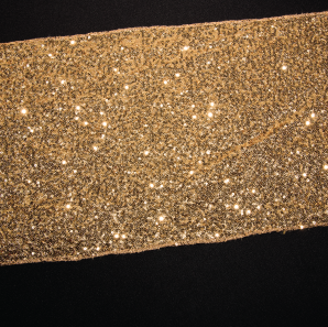 Close up of a gold sequined table runner.