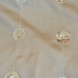 Close up of a gold sequined overlay.