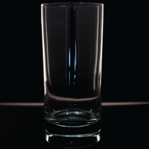 Close up of a highboy glass in front of a black backdrop.