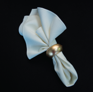 Close up of an ivory colored napkin in a gold napkin ring.