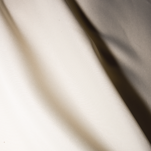 Close up of an ivory colored polyester tablecloth.
