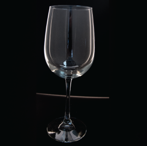 Close up of a large wine glass in front of a black backdrop.
