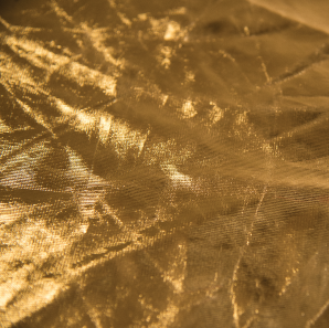 Close up of a metallic gold colored spandex tablecloth.