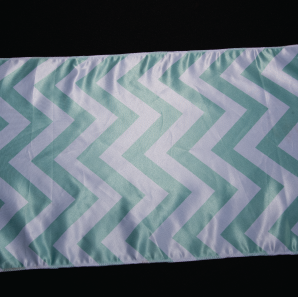 Close up of a mint colored chevron striped table runner.
