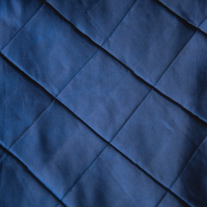 Close up of a navy blue tuck tablecloth.