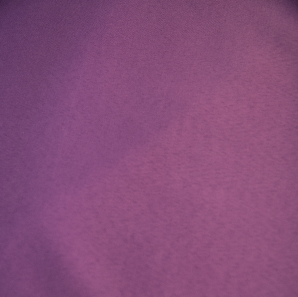 Close up of a purple polyester tablecloth.