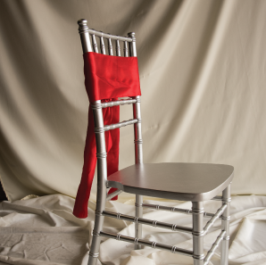 Front of a red chair sash tied into a bow on a silver chair.