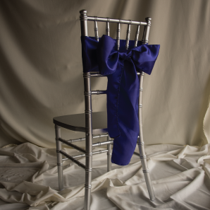 Back of a royal blue chair sash tied into a bow on a silver chair.