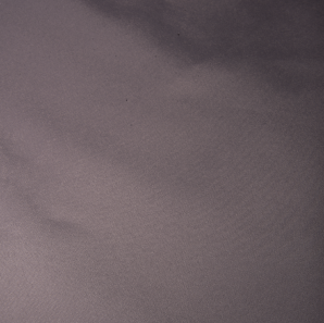 Close up of a silver colored polyester tablecloth.