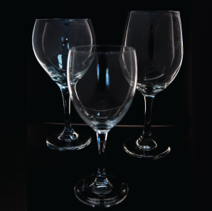 Close up of three small wine glasses in front of a black backdrop.