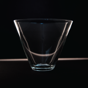 Close up of a stemless martini glass in front of a black backdrop.