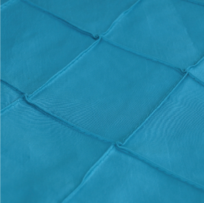 Close up of a turquoise pin tuck tablecloth.