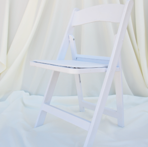 White resin garden chair in front of a white backdrop.